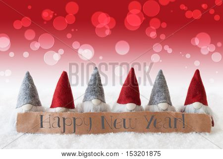 Label With English Text Happy New Year. Christmas Greeting Card With Red Gnomes. Bokeh And Christmassy Background With Snow.