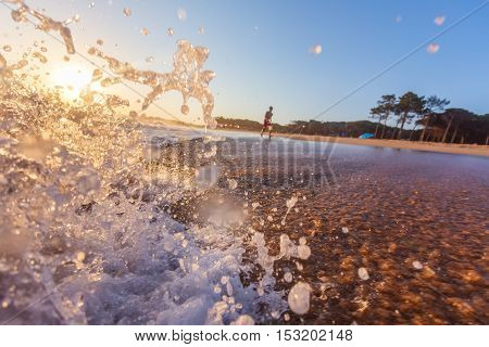 Blue Ocean Wave Crashing at Sunrise. In Portugal.