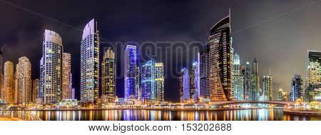 Panoramic view of Dubai Marina bay with yacht and cloudy sky, Dubai, UAE.