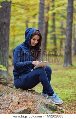 Beautiful happy young woman surfing the web and reading on a tablet in autumn forrest enviroment