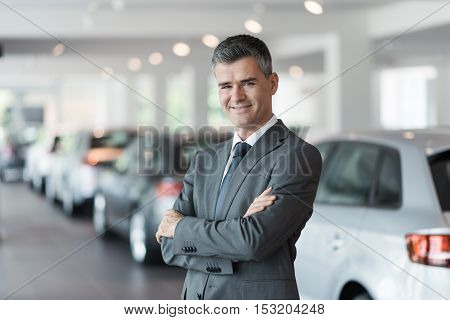 Confident Car Salesman At The Showroom