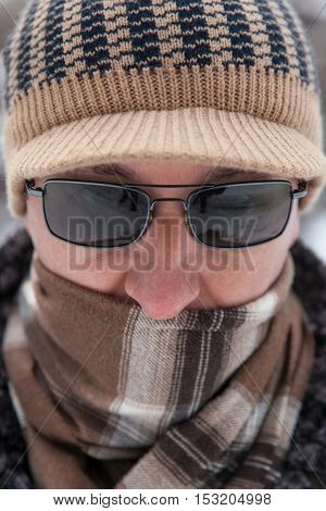 Portrait of an adult man in knitted cap scarf and sunglasses outdoors in winter day closeup
