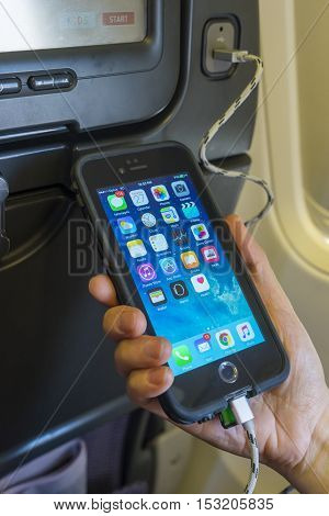 Brisbane, Australia - September 27, 2016: View of a passenger charging a mobile phone onboard an airplane with USB port at the seat.