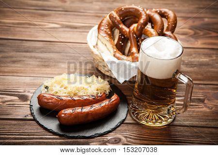 Pretzels, bratwurst and sauerkraut on wooden table