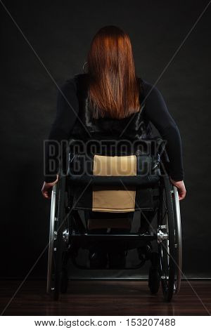 Health invalid disability sad negative tragedy concept. Backside of disabled person. Handicapped lady sitting on wheelchair.
