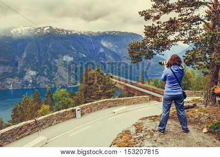 Tourism vacation and travel. Woman tourist taking photo with camera enjoying Aurland fjord view from Stegastein viewpoint Norway Scandinavia. poster