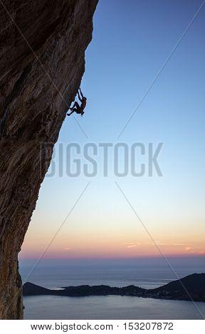 Rock climber on overhanging cliff at sunset. Kalymnos Island, Greece.