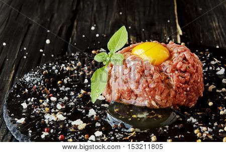 Steak tartare of raw minced meat with salt and spices, on a black background, selective focus, space for text