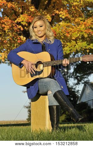 Beautiful blond asian woman playing guitar outdoors with autumn tree in the back