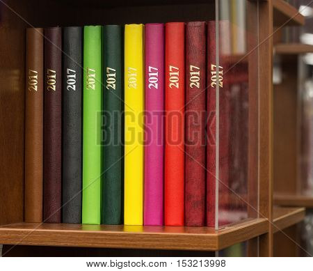 Color books with inscription 2017 on wooden shelf with glass partition. on the book