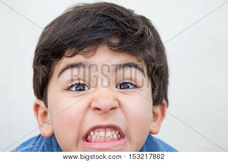 Grimacing boy stares and shows his teeth