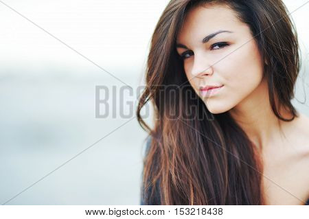 Head beautiful long haired young brunette woman with half-closed eyes on blurred sky background closeup.