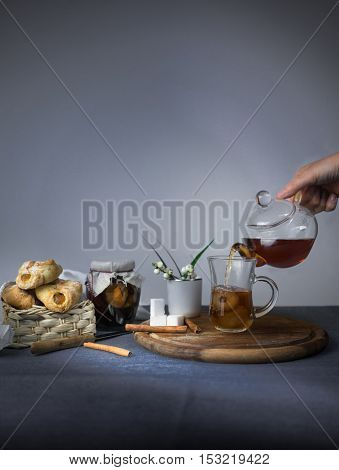 female hand pouring tea from a teapot into glass cup