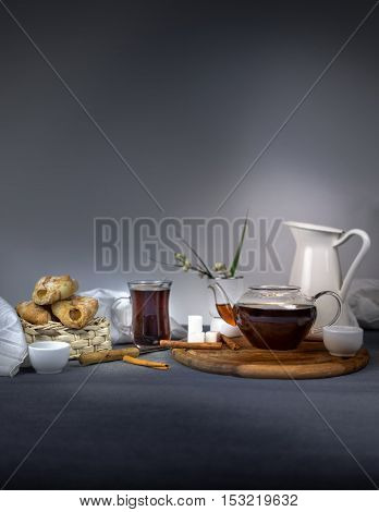 Still life with a jar of plum jam, fresh bread rolls, a glass cup and teapot on a wooden table.