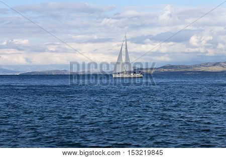 White yacht gliding through a blue bay