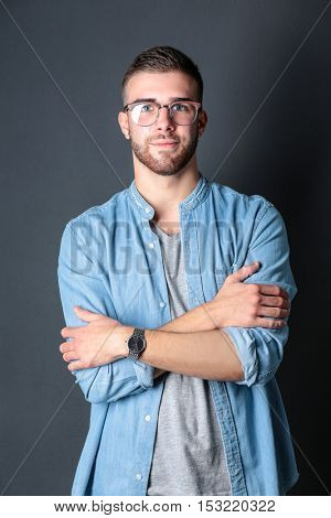 Portrait of happy casual man standing isolated on a dark background