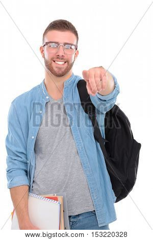 Young male student with a school bag holding books and pointing you isolated on white background