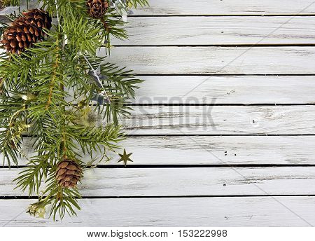 pine bough with Christmas gold and silver star decorations on rustic gray wood