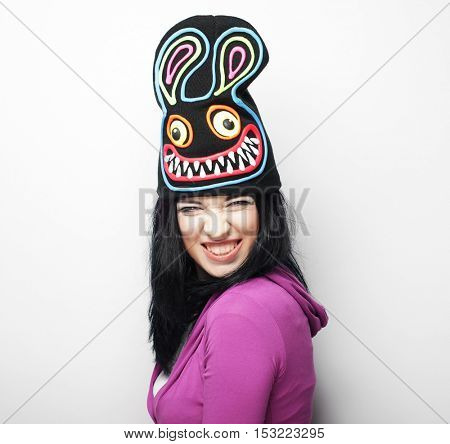 Playful young woman in funny hat with rabbit