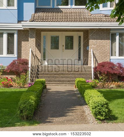 Entrance of family house with small hedges on sides in suburban area of Vancouver Canada