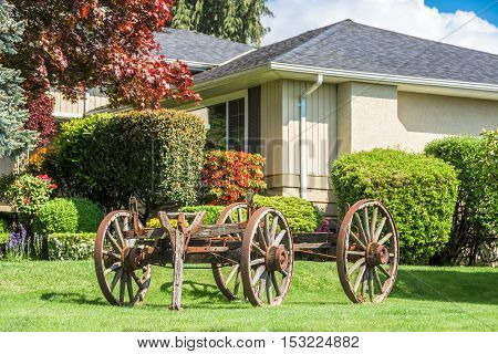 Creatively landscaped yard in residential community with old horse vehicle on green lawn