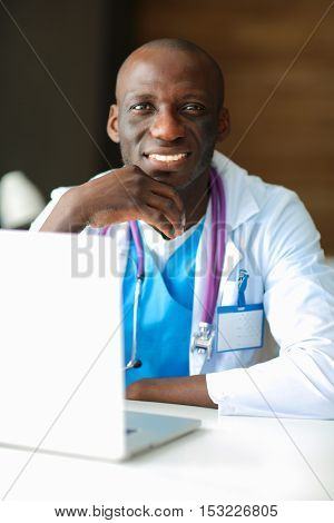 Young african doctor working on laptop at desk