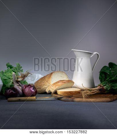 still life. jug, bun, onion garlic on a blue tablecloth