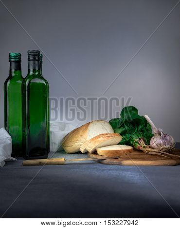 still life. jug, bun, onion, garlic, spinach on a blue tablecloth space for text