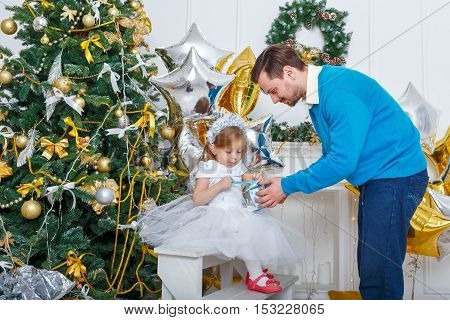 Father and daughter unpacked gifts at the Christmas tree. The father gives his daughter a gift a little sweet girl unties the ribbon. The festive mood. Family celebration.