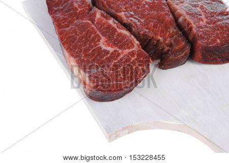 three fresh raw marble beef meat sirloin porterhouse steak on light wood cut board isolated on white background