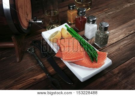 fresh raw salmon fillet served with lemon and white wine in wineglass, wooden barrel, bottle, on white plate over vintage wood table with handmade cutlery knife and fork