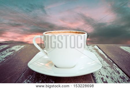 Hot coffee on old wood table with background of sky - soft focus