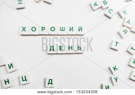 Good Day made from russian scrabble blocks. Crossword game with constructed combination and single tiles with letters, white background