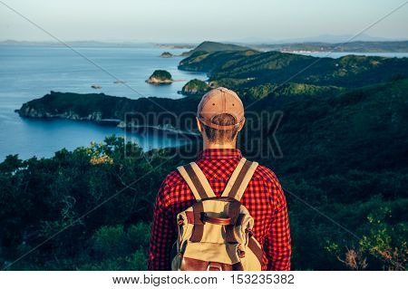 Male traveler from back on the sea coast looking forward
