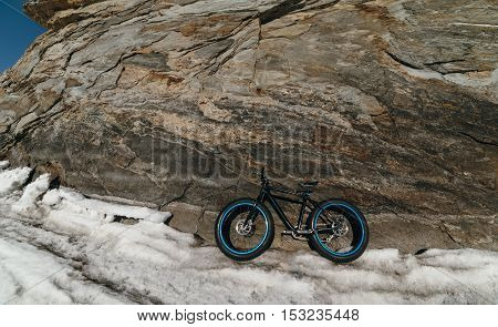 Fatbike also called fat bike or fat-tire bike - Cycling on large wheels. Bike standing on the ice of Lake Baikal, on the background of the island with a small cave gorge .