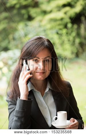 middle-aged woman in business suit drinks cup of coffee and uses smart phone