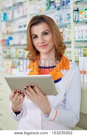Female pharmacist checking medicine availability on her tablet