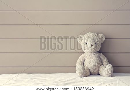 vintage teddy bear sit on the right side white bed at headboard and brown wall background for gift and surprise