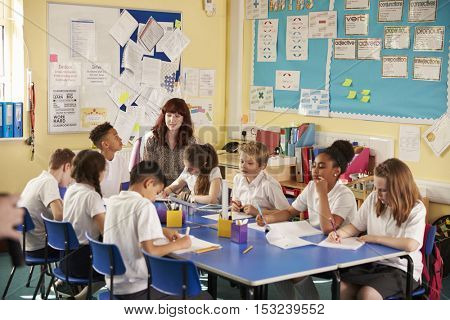 Primary school teacher with kids working on a class project