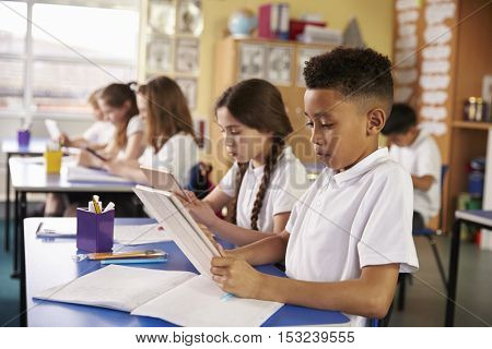 Kids use tablet computers in primary school class, close up