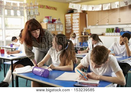 Primary school teacher helps a pupil at desk with classwork