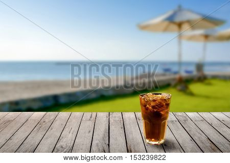 Image of cola in glass with ice on front with blurred background of sea and beach.