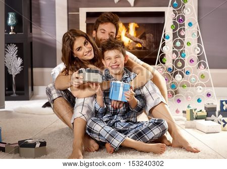 Attractive young family having fun at christmas morning in pajamas on floor by christmas tree.