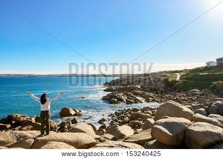 Woman standing at the edge of the rock and looking into the sea at Port Elliot South Australia