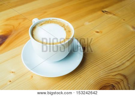 Coffee cup and saucer on wooden table at cafe.