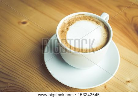 Coffee cup and saucer on wooden table at cafe. Top view