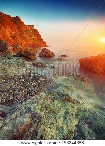Seascape during sunset. Beautiful natural seascape. Stones at foreground