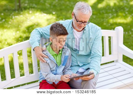 family, generation, technology and people concept - happy grandfather and grandson with tablet pc computer at summer park