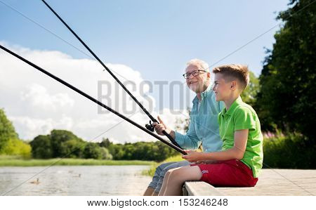 family, generation, summer holidays and people concept - happy grandfather and grandson with fishing rods on river berth poster