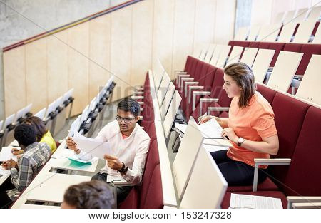 education, high school, university, learning and people concept - group of international students with tests at lecture hall